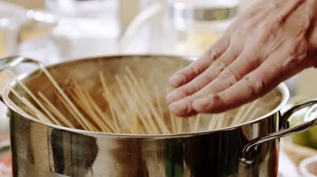 Boiling spaghetti pasta in a steel pot. Slow motion