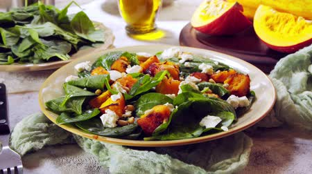 Roasted pumpkin salad with spinach, feta, tomatoes and pine nuts. Autumn dish. Стоковые видеозаписи