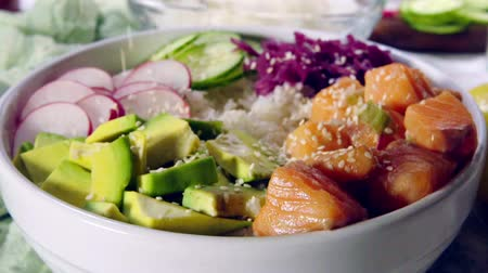 тыкать : Poke bowl, traditional Hawaiian raw fish salad with rice, avocado, cucumber and radish. Slow motion Стоковые видеозаписи