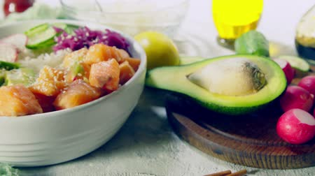 тыкать : Poke bowl, traditional Hawaiian raw fish salad with rice, avocado, cucumber and radish Стоковые видеозаписи