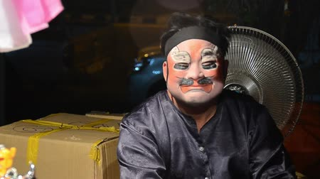 Пекин : Asian actor from a traveling theater making the makeup behind the stage