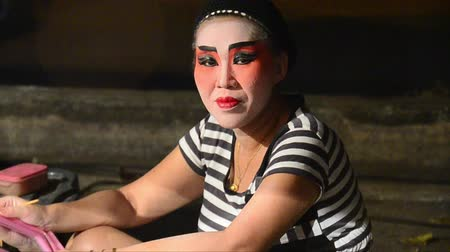 ator : Asian actor from a traveling theater making the makeup behind the stage