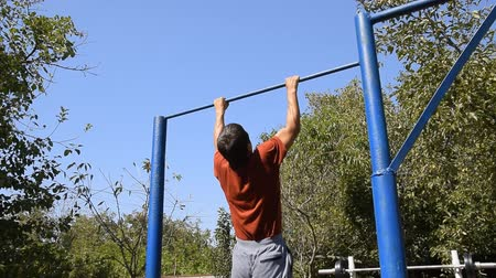 testépítés : man pulls himself up on the bar. Playing sports in the fresh air. Homemade Horizontal bar in the backyard Stock mozgókép