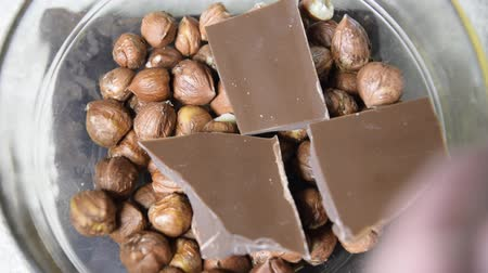 caloric : Milk chocolate and hazelnut in a glass cup. Chopped chocolate bars and hazelnuts. Stock Footage