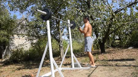 squat : man takes a bar to perform squats. Exercises in bodybuilding. sport in the backyard