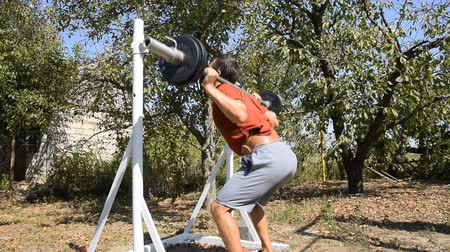 squats : man takes a bar to perform squats. Exercises in bodybuilding. sport in the backyard
