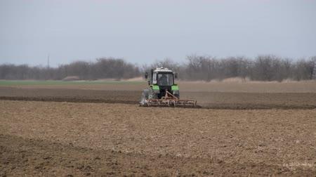 trator : Lush and loosen the soil on the field before sowing. The tractor plows a field with a plow.