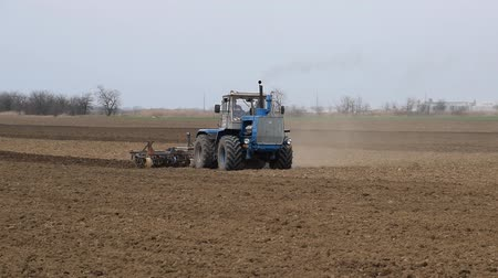 bum : Lush and loosen the soil on the field before sowing. The tractor plows a field with a plow.