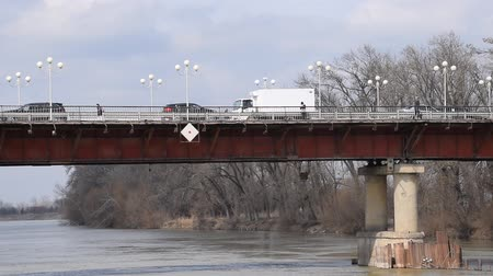 suspension : Automobile bridge over the river. On the bridge cars go and people go.