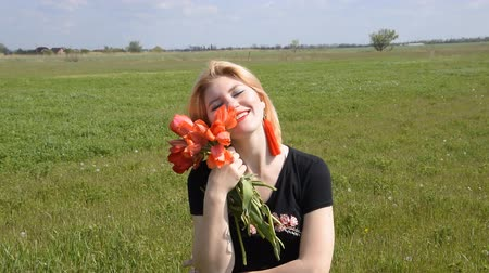 outing : The blonde smells a bouquet of tulips. Girl with a bouquet of tulips flowers. Stock Footage