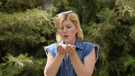 foukání : A blond woman blowing a poplar fluff. Poplar fluff in the hands of a girl