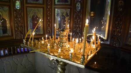 Burning candles on a stand near the icons in the chapel. Attributes of Orthodox Christianity. Стоковые видеозаписи