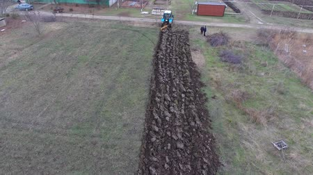 трактор : Tractor plowing the garden. Plowing the soil in the garden. Plowing field