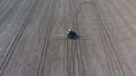 fertilizing : Tractor with hinged system of spraying pesticides. Fertilizing with a tractor, in the form of an aerosol, on the field of winter wheat