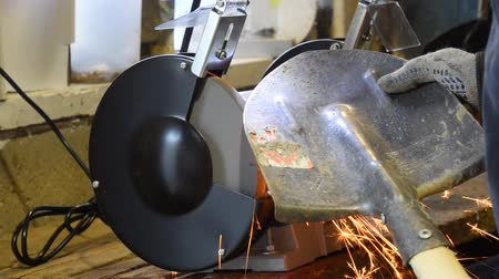 jiskry : Sharpening a shovel on a grinding machine. Electric sharpened.