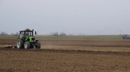 ploughing : Lush and loosen the soil on the field before sowing. The tractor plows a field with a plow