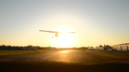 Small airplane approaching with blue sky and landing at the airport with sunset.