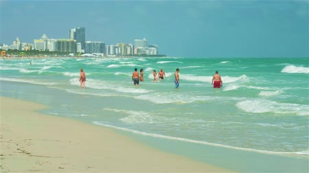 Miami Beach, Florida - February 22, 2018: Super high definition video of visitors enjoying the warm winter weather along the shoreline in popular South Beach on a windy day.