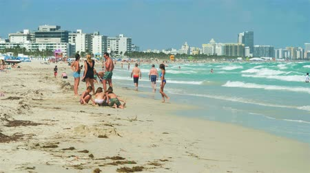 visitantes : Miami Beach, Florida - February 22, 2018: Super high definition video of visitors enjoying the warm winter weather along the shoreline in popular South Beach on a windy day.