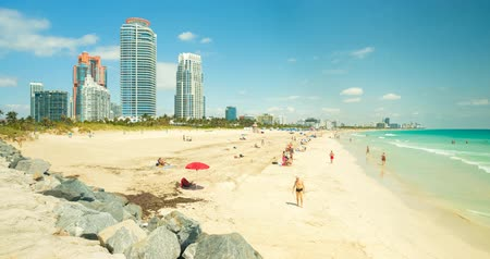 купальный костюм : Miami Beach, Florida USA - April 11, 2018: High definition time lapse video of visitors enjoying the warm spring weather along the shoreline in popular South Beach on a sunny day.