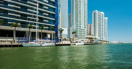 Miami, Florida USA - April 16, 2018: Time lapse video of the Miami River along the downtown district with boats cruising by the modern skyscrapers.