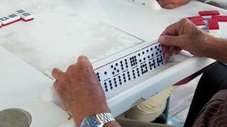 eight : Slow motion high definition video of an elderly individual man playing the popular domino game.