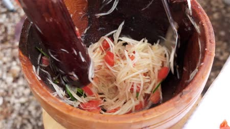 chili : Slow motion high definition video of the muddling preparation in the making of Thai green papaya salad.