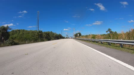 Miami, Florida USA - February 7, 2019: High definition motion time lapse video of a automobile driving through the Florida Everglades.