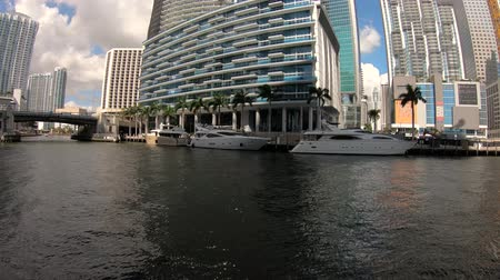 набережная : Miami, Florida USA - February 15, 2019: Motion time lapse video of the Miami River along the downtown district with boats cruising by the modern skyscrapers.