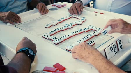 eight : High definition close up video of elderly individuals playing the popular domino game at the historic Domino Park in Little Havana in Miami.