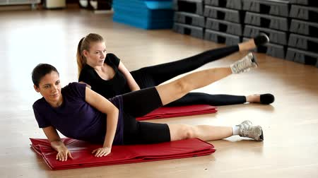aeróbica : Two young women training in the aerobic room. compilation of couple exercises: leg lifting, abdominal, superman, stretching Vídeos