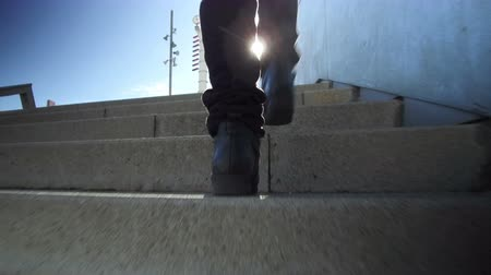 pursue : Climbing a stairs, low angle shot. Following some feet that go up to concrete stairs.Back view. Abstract Concept of improve, success, effort.
