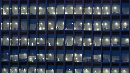 exterior : Office building, with illuminated interior at dusk, in the city of Barcelona.Motion Camera Panning Right and zoom out