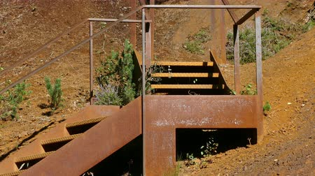 reddish : Iron ladder in the mountain hillside. Close-up old and rusty staircase in an iron mine area with vegetation moved by the breeze in Andorra. Stock Footage