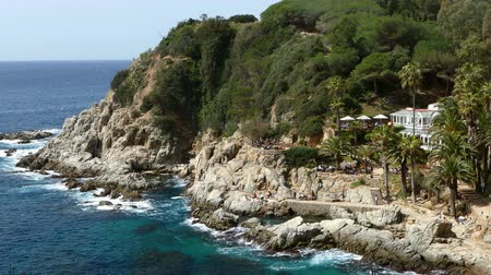 pino : Seascape of the COSTA BRAVA in Catalonia.Time Lapse. View of cliff over the sea, municipality of LLoret province of Girona, with a public bar in an idyllic setting.