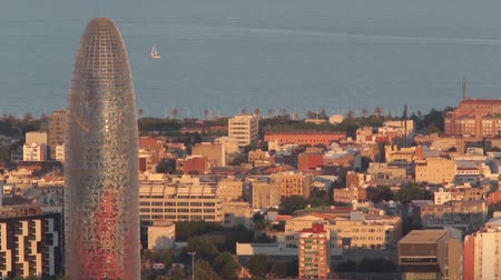 architecture and urbanism : Sunset view of the Agbar tower in Barcelona with movement of sailboats in the sea.Time Lapse