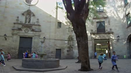 recess : Ancient Barcelona, ??Gothic Quarter.Panoramic view of the St. Felip Neri square, with students playing at recess. Smooth camera movement: panning left.