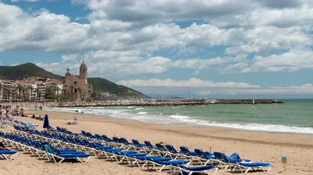 hyper : Cinemagraph of wide view of SITGES. Smooth camera movement: Zoom in.Hyper lapse. Village of the province of Barcelona (Catalonia), a springtime sunny day with the fast motion of clouds and with static movement waves and activity of people.Three seconds