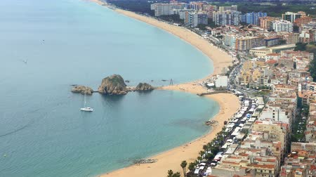 ancorado : Aerial view of BLANES, beaches, seafront, and town.Time lapse. Village of the province of Girona (Catalonia), wide panoramic with movement of people and traffic.