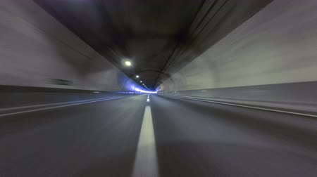 road tunnel : Fast driving at a empty tunnel.Vehicle shot Circulating quickly through a tunnel without traffic and at the end you come to the exit with fade in white. Time Lapse - Vehicle shot - Point of view - Long exposure - 4K resolution. Tunnel Dos Valires Stock Footage