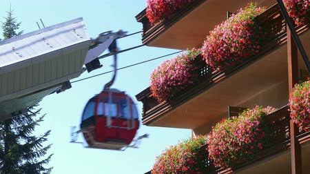 vazo : Cable way that ascends and descends next to balconies with planters full of flowers, in the town of La Massana, Andorra.