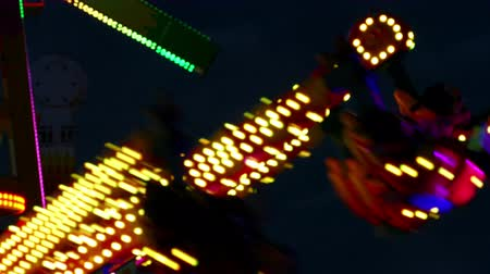 tontura : Close-up of attractions of fair, with colored flashing lights and turning at night.