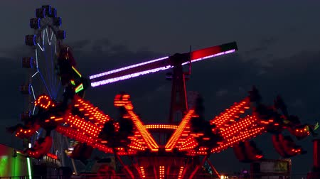 szédülés : Attractions of fair, with colorful lights and moving at sunset.