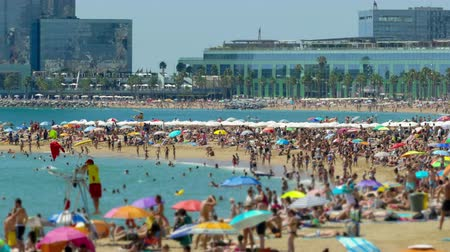 tilt shift : Activity on the beaches of the city of Barcelona with modern buildings background, a sunny summer day.Time lapse.Tilt-shift effect.4k.
