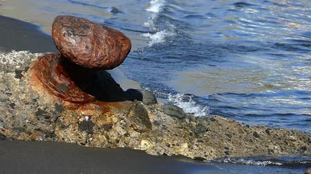 moorage : Closeup of a rusty old bollard on the beach, with waves in motion.Slow motion Stock Footage