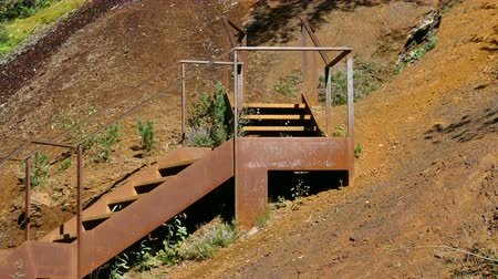 brilho intenso : Iron ladder in the mountain hillside. Close-up old and rusty staircase in an iron mine area with vegetation moved by the breeze in Andorra. Vídeos