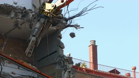 reinforced concrete : Close-up of heavy demolition machinery at work, pulling wall and beam. Stock Footage