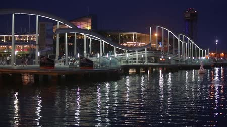 akşam vakti : Night view of Rambla de Mar, footbridge modern design in the port of Barcelona, ??a must for visitors to walk into town.