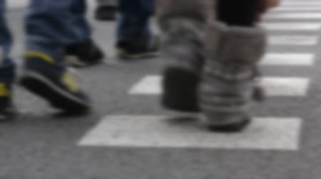 desfocado : Blurred detail of feet across a crosswalk front and back view, on a street in Barcelona.