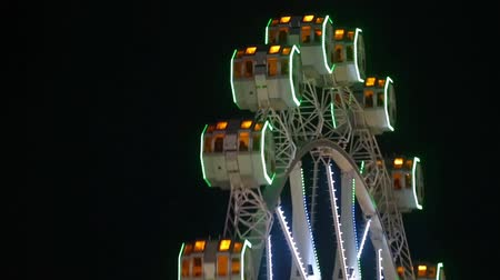 szédülés : Close-up of Ferris wheel by rotating at night with large colorful of led lights and motion.Normal speed